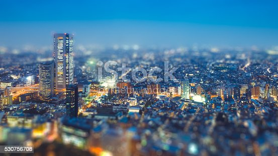 istock Tilt shift Photo High-rising buildings lighting up in tokyo 530756708