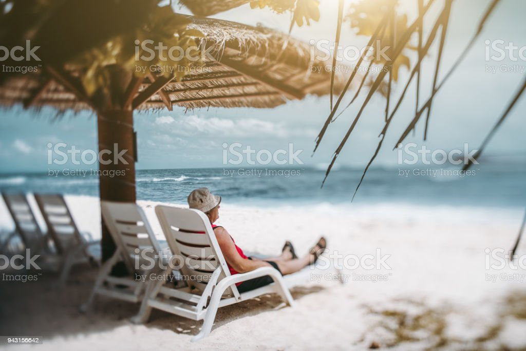 Tilt shift view of old man on the beach recliner stock photo
