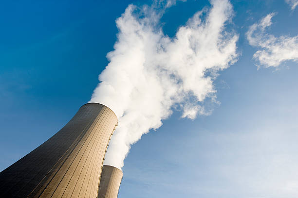 Tilt Shot of Two Steaming Cooling Towers with blue sky stock photo