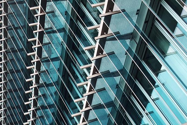 tilt view of louvered structural glass wall of office building - com portada imagens e fotografias de stock