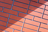 Background brick wall of red brick in three rows with a shadow inclined to the side