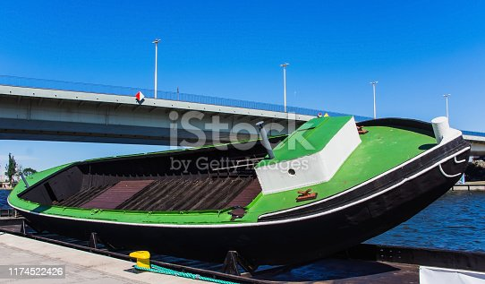 Large tilted empty boat on docking ramp on the embankment of Odra River, Szczecin, Poland
