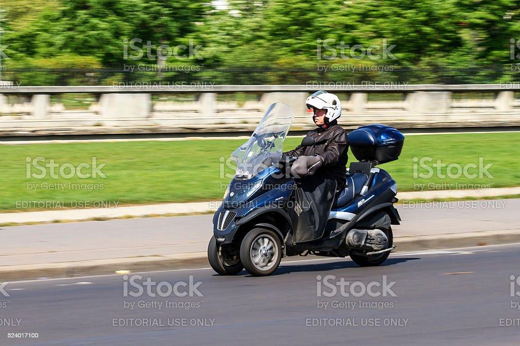 Tilting three-wheeler commute stock photo