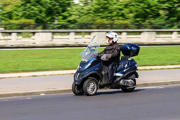 Tilting three-wheeler commute Paris, France - April 15, 2014: Business man travelling to work on a tilting three-wheeler in Paris, France, on April 15, 2014 three wheel motorcycle stock pictures, royalty-free photos & images