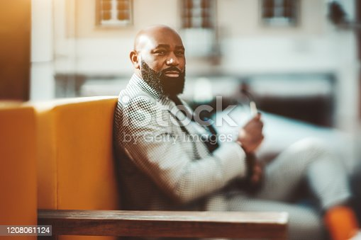 True tilt-shift portrait with a selective focus on the part of the face of an adult handsome bald African guy with a neat beard and in a plaid elegant costume sitting on an orange sofa outdoors