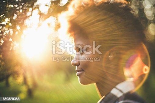 istock Tilt-shift portrait of black girl in front of sunset 689829386