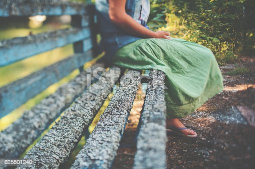 istock Tilt-shift view of bench with girl sitting on it 625801240