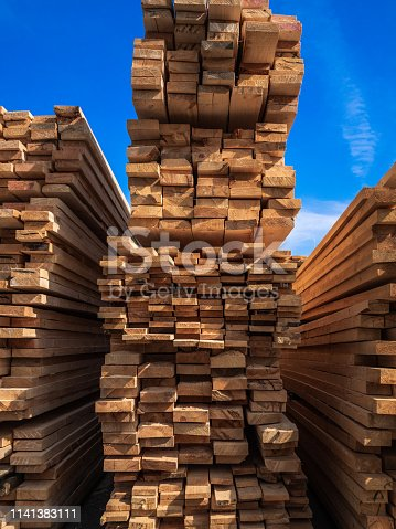 Timber for sale. The wooden boards put at each other into storage of shop. Blue sky
