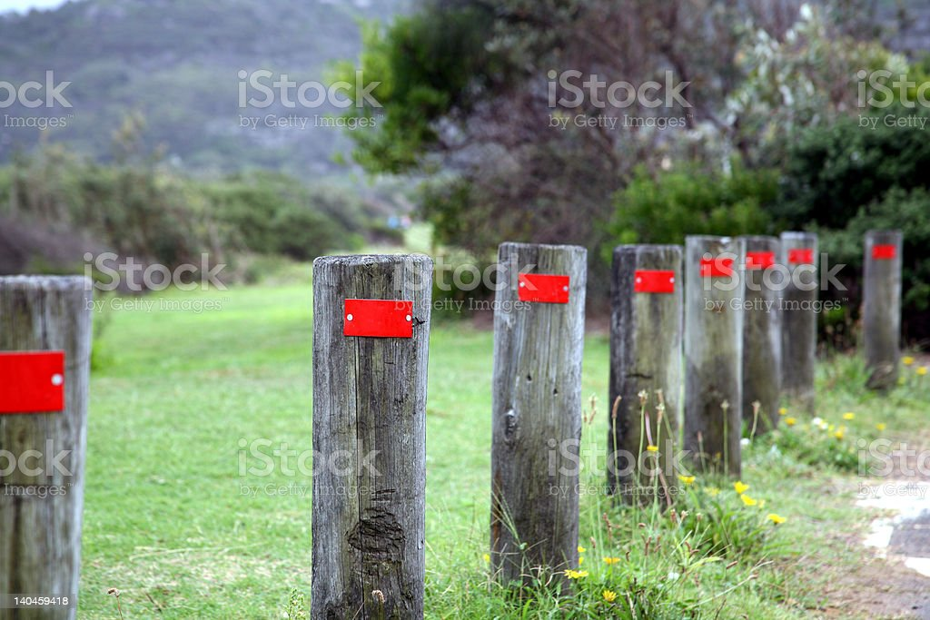timber posts with red reflectors by roadside stock photo