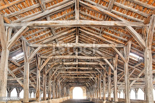 Horizontal composition photography of oak beams, wood building structure in a row pattern, below the halls (les halles) of Cremieu medieval city in Isere, Rhone-Alpes region in France (Europe). Architecture of the late Middle Ages, the hall is dated 1434 (15th century) by analyzes of the wood framing.