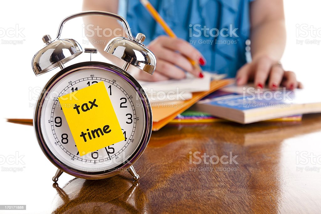Time:  Alarm clock, income tax time note.  Woman background. Reminder. royalty-free stock photo