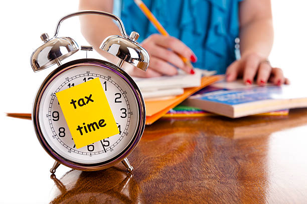 Time:  Alarm clock, income tax time note.  Woman background. Reminder. stock photo