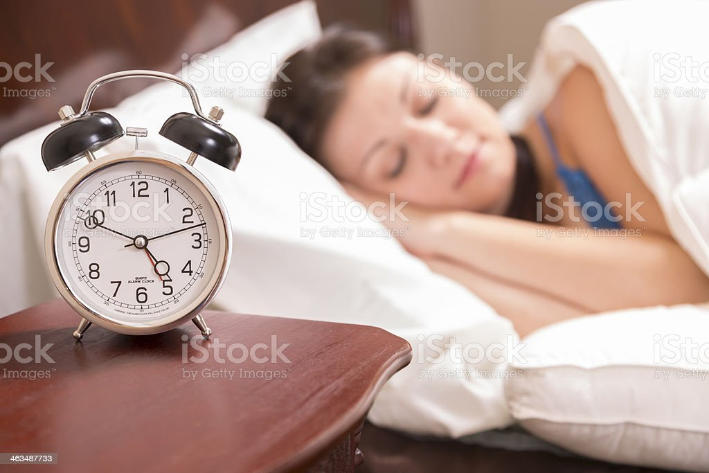 Time:  Alarm clock shows early time. Woman is peacefully sleeping. stock photo