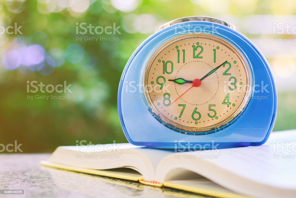Time And Learning Blue Alarm Clock On An Opened Book Against