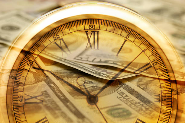 Time and Money. Clock in US dollars - Stock Image Time is money.  Clock in US dollars Clock, shot with very shallow depth of field time is money stock pictures, royalty-free photos & images