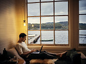 Shot of a young man using a laptop while relaxing in his holiday home