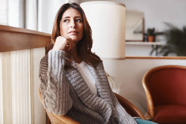 Time away to process her thoughts Shot of an attractive young woman relaxing on a chair at home introspection stock pictures, royalty-free photos & images