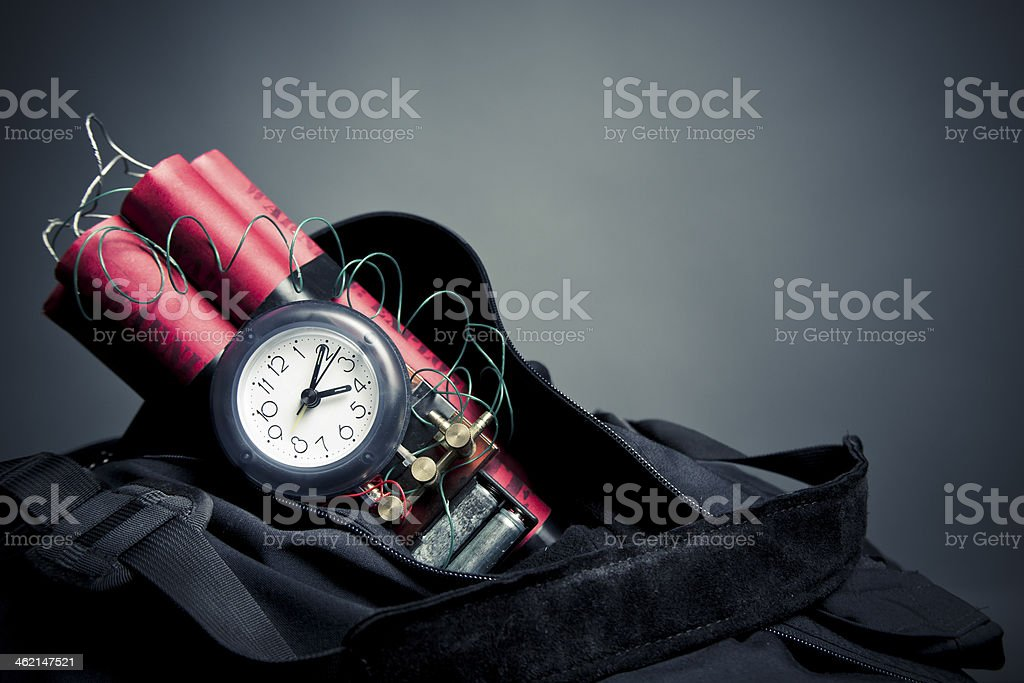 Time bomb sticking out of backpack on grey background stock photo