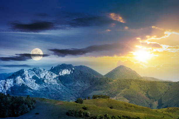 time change above mountains with rocky formations day and night time change concept above mountains with rocky formations. grassy meadows, forested hills and huge cliffs. wonderful nature scenery. beautiful weather in springtime with sun and moon fresh start morning stock pictures, royalty-free photos & images