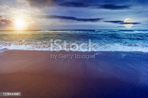 day and night time change concept above sandy beach and turquoise sea. great view of waves rolling to the coastline. wonderful weather with glowing sky with sun and moon