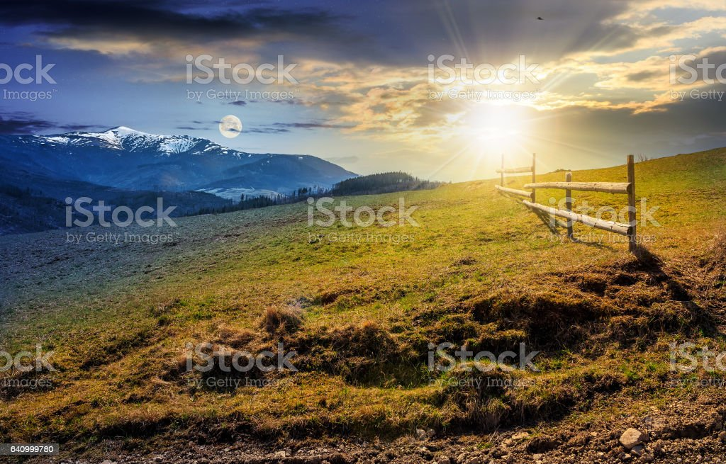 time change concept. fence on rural field in spring stock photo