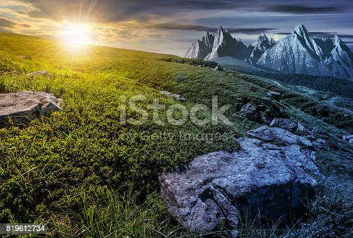 1074120624 istock photo time change concept. meadow with huge stones on top of mountain range 819612734