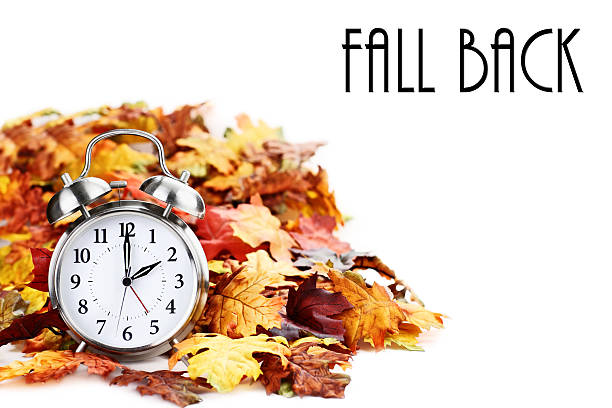 Time Change Daylight Savings with Text Alarm clock in colorful autumn leaves isolated against a white background with light shadow and shallow depth of field. Daylight savings time concept. daylight savings stock pictures, royalty-free photos & images