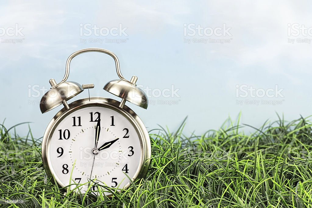 Time change reminder with clock on lawn stock photo