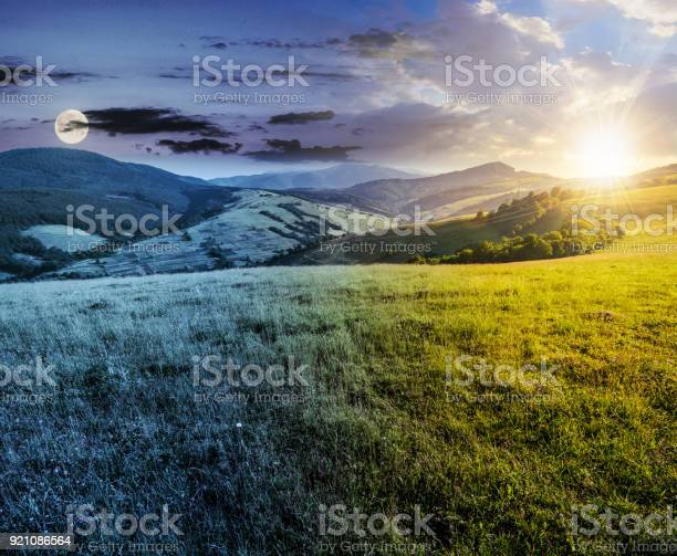 Photo of time changes over grassy meadow in mountains