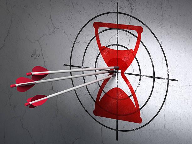 time concept: arrows in hourglass target on wall background - zandloper icoon stockfoto's en -beelden