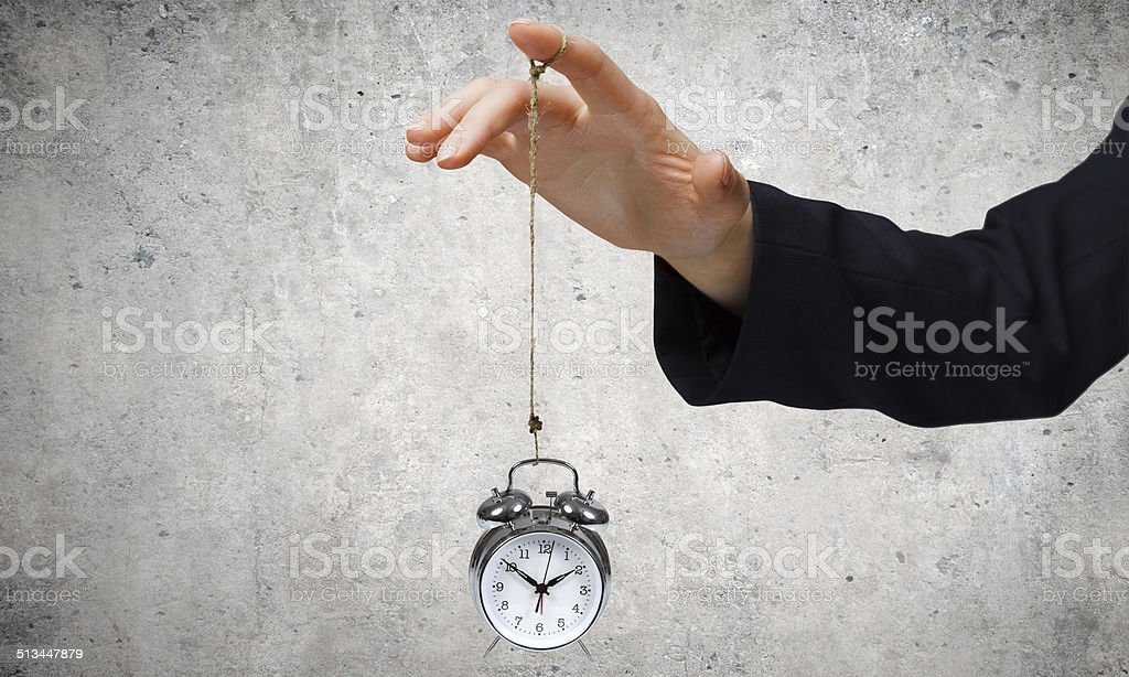 Time concept Close up of businessman holding clock on rope Abstract Stock Photo