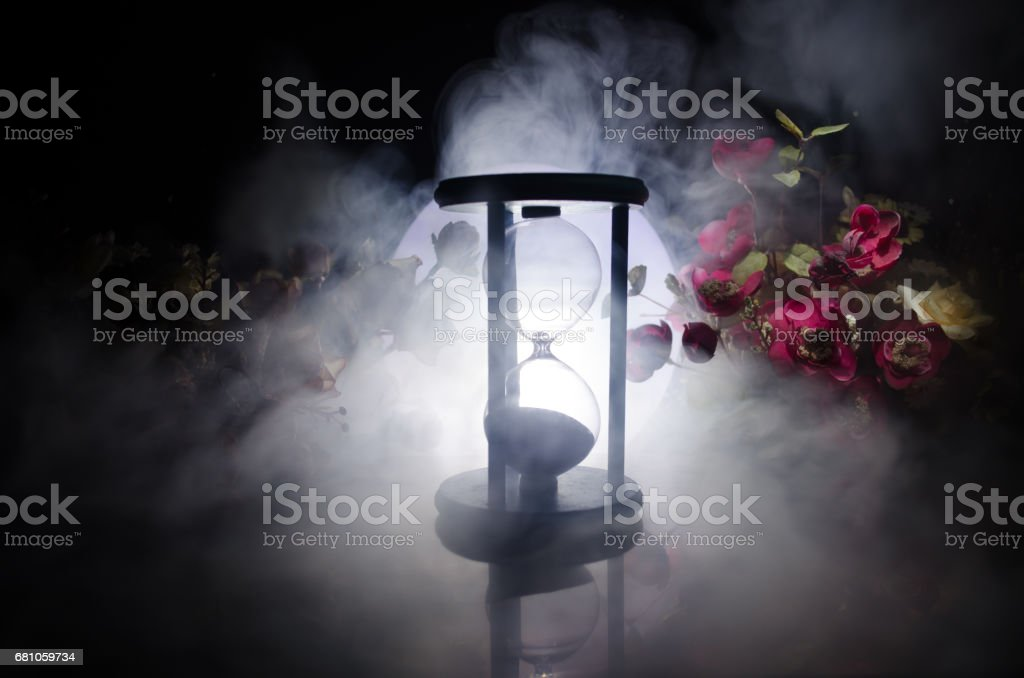 Time concept. Sand passing through the glass bulbs of an hourglass measuring the passing time as it counts down to a deadline. Silhouette of Hourglasses in smoke on dark background. With flowers royalty-free stock photo