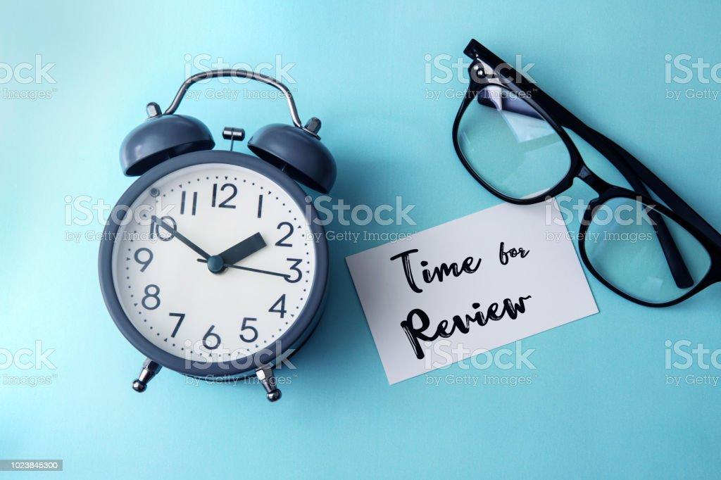 Time concept with  paper note of Time fo Review  message , alarm clock with a reading eyeglasses decoration on blue background stock photo