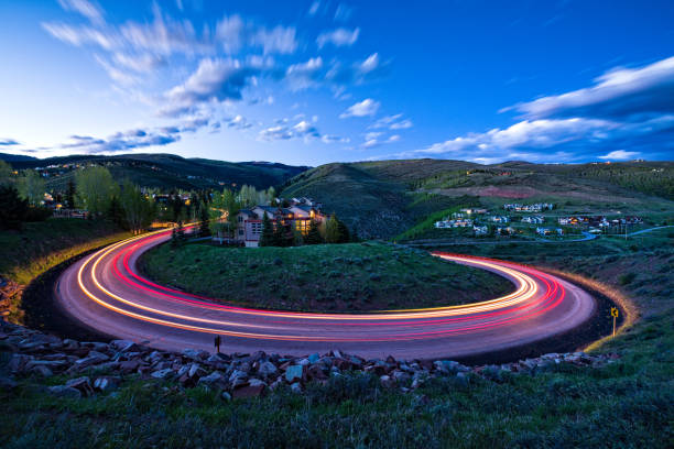 Time Exposure Loop Road Switchback at Dusk Time Exposure Loop Road Switchback at Dusk - Wildridge, Avon, Colorado USA. Road with tight round switchback and cars driving up and down road. avon colorado stock pictures, royalty-free photos & images