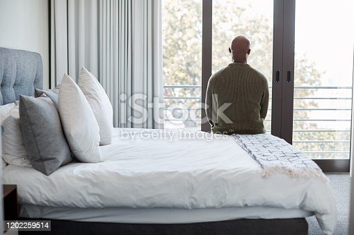 Rearview shot of a mature man looking through a window in a bedroom at home