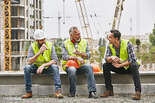 Time for a break. Group of builders in working uniform are eating sandwiches and talking while sitting on stone surface against construction site. Building concept. Lunch concept. Building concept