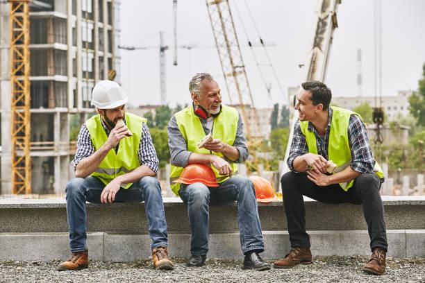 dags för en paus. grupp av byggare i arbetar uniform äter smörgåsar och pratar medan du sitter på stenytan mot bygg arbets platsen. bygg koncept. lunch koncept - ta en paus bildbanksfoton och bilder