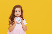 Time for a party. A pensive cute child in a fancy dress holds a small alarm clock in his hands and shows up. Yellow studio background.\