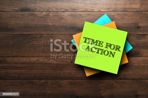 istock Time For Action, the phrase is written on multi-colored stickers, on a brown wooden background. Business concept, strategy, plan, planning. 956960320