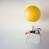 A newborn baby in a small air balloon with his stuffed animals