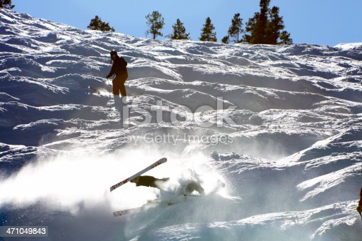 A skier falling on a challenging bump run.  Strong natural backlighting, creates a
