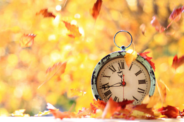 Time for autumn, season change Autumn leaves blowing in the wind across an antique alarm clock time zone stock pictures, royalty-free photos & images
