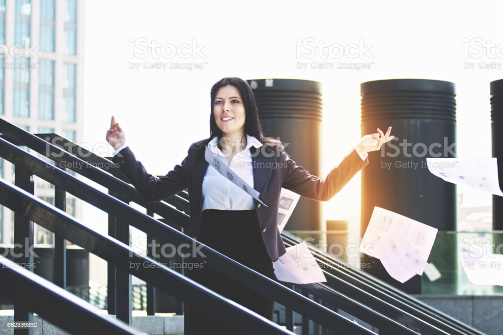 Time for brake. Portrait of attractive and full of energy business woman in smart casual clothes throwing paper documents away while standing near office building. foto stock royalty-free