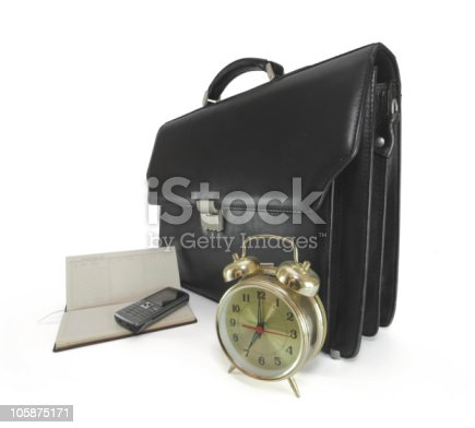 Leather briefcase, alarm clock, mobile phone and organizer isolated on white background
