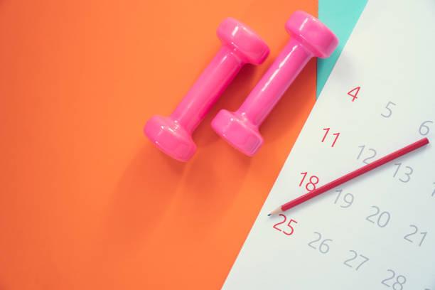dags för att träna kalender och hantel med färgglad bakgrund på bordet - calendar workout bildbanksfoton och bilder