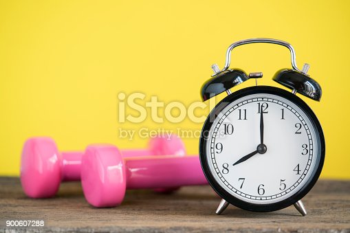 istock Time for exercising clock and dumbbell with colorful background 900607288