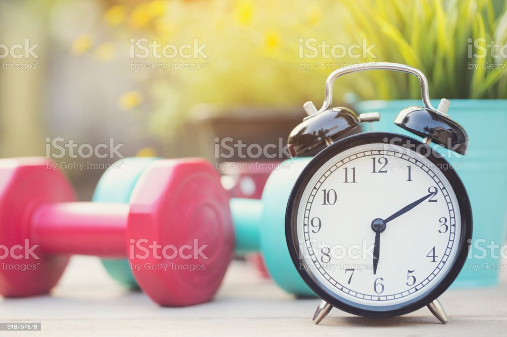 Time for exercising clock and dumbbell with colorful background stock photo