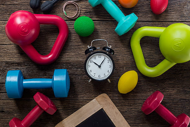 time for exercising clock and fitness equipment on table backgro - trainer uhr stock-fotos und bilder