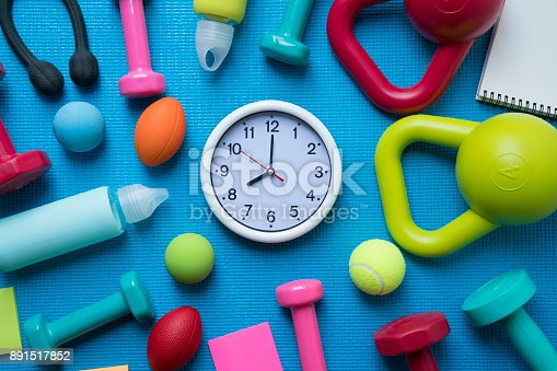 istock Time for exercising clock and fitness equipment with yoga mat background 891517852