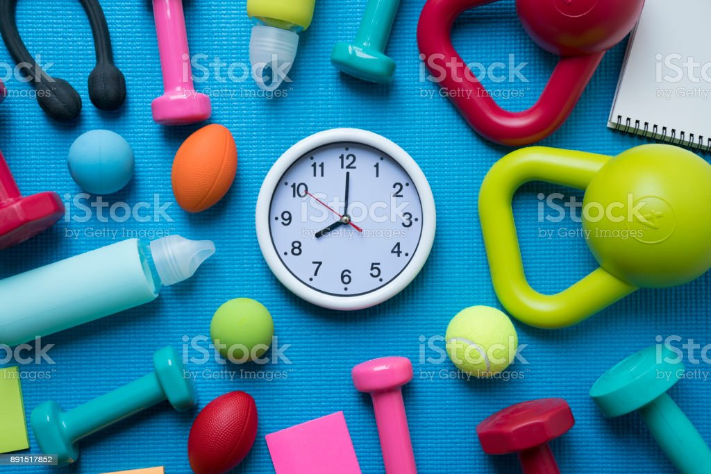 Time for exercising clock and fitness equipment with yoga mat background stock photo